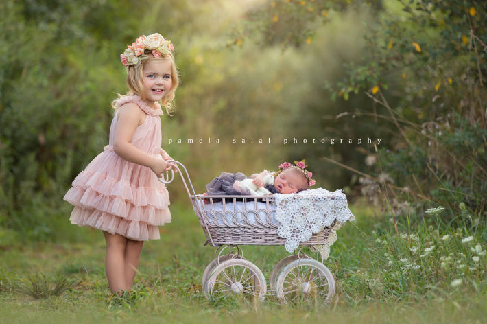 Pamela salai photography outside newborn posing with sister